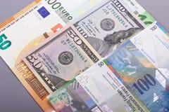 100欧元50美元,瑞士法郎灰色背景 免版税库存照片