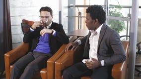 欧洲人和非裔美国人供以人员坐在扶手椅子并且谈判 影视素材
