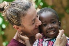 欧洲妇女画象有一个非洲黑人男孩的 免版税库存图片