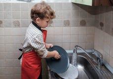 欧洲男孩在家洗盘子 图库摄影