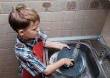 欧洲男孩在家洗盘子 免版税库存图片