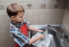 欧洲男孩在家洗盘子 库存照片