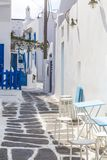 欧洲 希腊 cyclades Mykonos海岛 在传统狭窄的街道上的一个庭院有蓝色门、台阶、桌和椅子的和 免版税库存照片