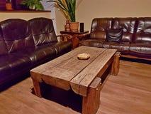 欧洲 波兰 内部客厅 用黑褐色皮革报道的一个软的木家具角落 一份巨型的木咖啡 免版税库存照片