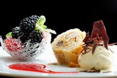 欧特烹调、果馅奶酪卷与冰淇凌和莓果点心在餐馆桌上 库存照片