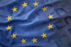 欧盟五颜六色的挥动的旗子在欧元金钱钞票背景的 库存图片