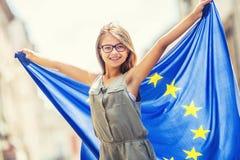 欧盟标记 有欧盟的旗子的逗人喜爱的愉快的女孩 挥动与欧盟旗子的年轻十几岁的女孩在城市 免版税库存照片