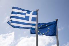 欧盟社区旗子和希腊飞行国旗从杆的 库存图片