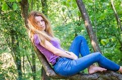欧洲出现年轻美好的性感的女孩模型与长的头发的在衬衣和牛仔裤坐树在的步行期间 免版税库存图片