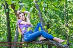 欧洲出现年轻美好的性感的女孩模型与长的头发的在衬衣和牛仔裤坐树在的步行期间 免版税库存照片
