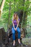 欧洲出现年轻美好的性感的女孩模型与长的头发的在衬衣和牛仔裤坐树在的步行期间 库存图片