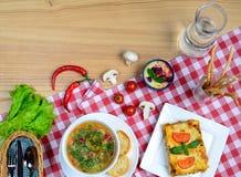 欧洲午餐-博洛涅塞蔬菜通心粉汤汤、的烤宽面条和蛋糕在一张木桌上服务 与拷贝空间的意大利食物背景 库存图片