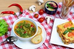 欧洲午餐-菜博洛涅塞蔬菜通心粉汤汤、的烤宽面条和蛋糕在一张木桌上服务 意大利背景 免版税库存照片