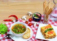 欧洲午餐-蔬菜汤、烤宽面条和点心在一张木桌上服务 与拷贝空间的意大利食物背景 免版税库存照片
