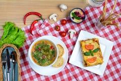 欧洲午餐-蔬菜通心粉汤汤、烤宽面条博洛涅塞和点心在一张木桌上服务 与拷贝空间的意大利背景 免版税库存照片