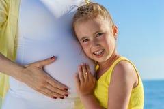 年轻欧洲女儿是她接近海的怀孕的可爱的妈妈的感人的肚子在蓝天下 免版税库存照片