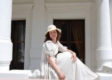 欧洲妇女坐在阳光下的和在葡萄酒的感人的头发在宫殿附近穿戴 免版税库存照片