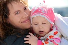 年轻欧洲妇女抱着她的困婴孩 图库摄影