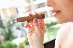 年轻欧洲妇女抽大雪茄,特写镜头 免版税图库摄影