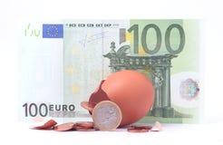 1欧洲硬币离开破裂的被孵化的鸡蛋在100欧元钞票附近 库存图片