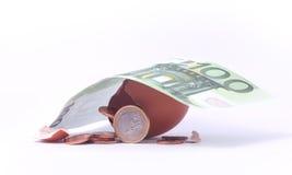 1欧洲硬币离开破裂的被孵化的鸡蛋在100欧元钞票以下 免版税库存图片