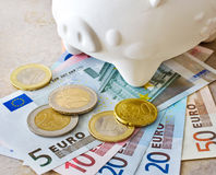欧洲钞票和硬币与存钱罐 免版税库存图片