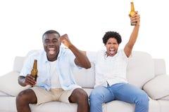 欲死欲仙的体育迷坐长沙发用啤酒 图库摄影