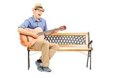 欲死欲仙的年轻吉他弹奏者坐长凳和唱歌 免版税库存照片