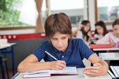 欺诈在书桌的男小学生在考试期间 免版税库存照片