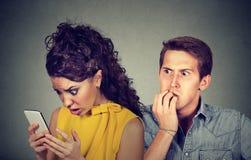 欺诈的男朋友 供以人员紧张地咬住的指甲盖,当在他的手机时的震惊女朋友读书正文消息 免版税库存图片
