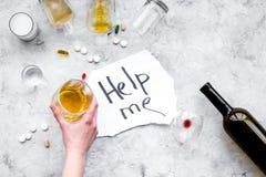 款待酒精依赖性 词在玻璃、瓶和药片附近帮助我在fgrey背景顶视图复制空间 免版税库存图片