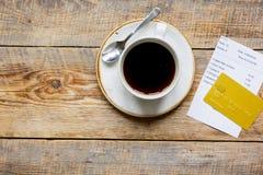 付款的咖啡和收据票据由在木桌背景顶视图大模型的信用卡 图库摄影