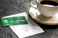 付款的咖啡和收据票据由在黑暗的桌背景的信用卡 免版税库存照片