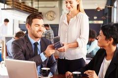 付付款的商人由在咖啡馆的电话 免版税库存图片