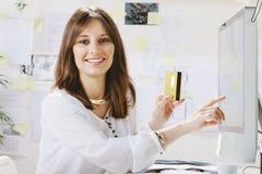 付付款的少妇创造性的设计师网上。 免版税库存照片