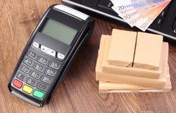 付款终端、货币欧元,膝上型计算机和被包裹的箱子在木板台 免版税库存照片