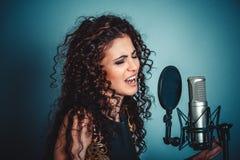 歌唱家 妇女唱歌与话筒唱歌的夫人女孩 免版税库存照片