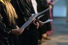 歌唱拿着乐谱和唱歌在学生gradu的歌手 免版税库存图片