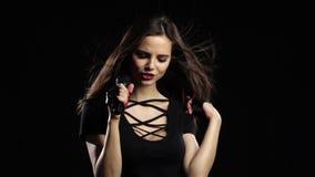 歌手在风唱精力充沛的歌曲,她的头发振翼 黑色背景 慢的行动 影视素材