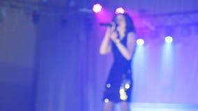 歌手女孩浅黑肤色的男人唱被弄脏的背景夜与话筒的美好的光 慢动作录影 歌手 股票录像