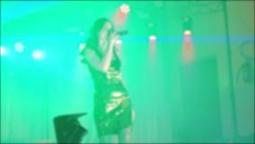 歌手女孩浅黑肤色的男人唱被弄脏的音乐会夜与话筒的美好的光 慢动作录影 歌手 股票视频