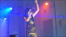 歌手女孩浅黑肤色的男人唱被弄脏的音乐会夜与话筒的美好的光 慢动作录影 歌手 影视素材