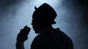 歌手转交的一半在握他的话筒和姿势示意的手的抽烟和白光的唱歌 投反对票 股票视频