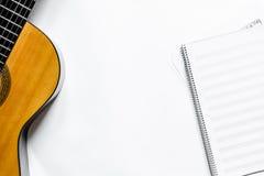 歌曲作者或dj有吉他和笔记本的工作地点白色背景顶视图大模型的 库存照片