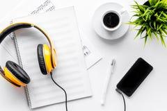 歌曲作者或dj有音乐笔记、机动性、耳机和白纸的工作地点白色背景顶视图嘲笑的 免版税库存照片