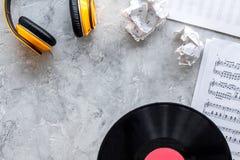歌曲作者或dj有vynil的在石背景顶视图大模型的工作地点和耳机 库存图片
