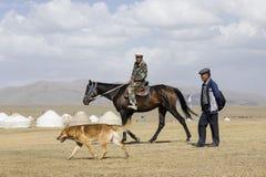 歌曲Kul,吉尔吉斯斯坦, 2018年8月8日:一吉尔吉斯在马和有他的狗步行的吉尔吉斯通过干草原 库存照片