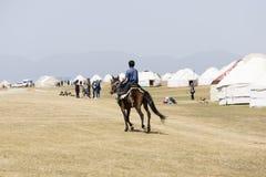 歌曲Kul,吉尔吉斯斯坦, 2018年8月8日:男孩骑马对Yurt阵营 免版税库存照片