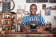 阻止一个新鲜的杯子热奶咖啡的微笑的咖啡馆barista 图库摄影