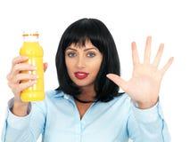 阻止一个瓶新鲜的橙汁的可爱的深色头发的少妇 免版税库存图片
